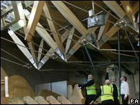 Parliament staff examine the loose beam