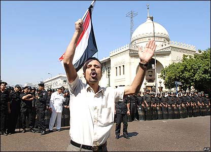 A protester waves an Egyptian flag in front of riot police