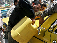 Palestinian taxi driver fills up with petrol bought at a Jewish settlement