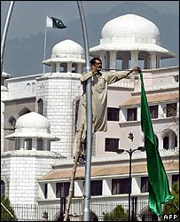 Preparing to hang an official banner in Islamabad