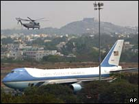 A helicopter, part of the US fleet carrying the president, flies over Air Force One in Hyderabad