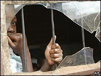 Child looking through a broken window