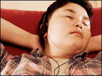 Teenage boy listening to music, BBC/Corbis