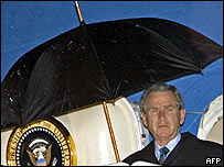 George Bush holding umbrella