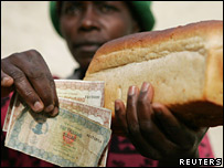 Zimbabwean woman holds money and a loaf of white bread