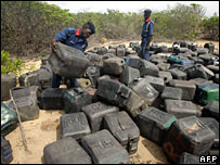 A policeman with dozens of jerry cans left on the beach