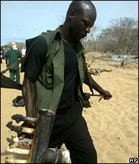 A Nigerian policeman carries metal piping at the site of the blast