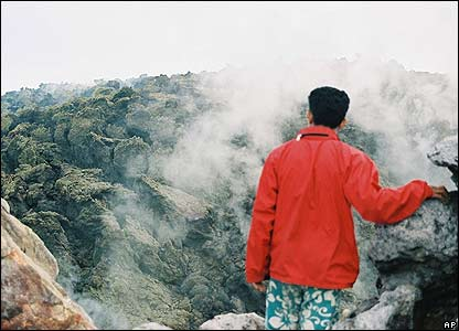 An unidentified man looks at cold lava from Mount Merapi