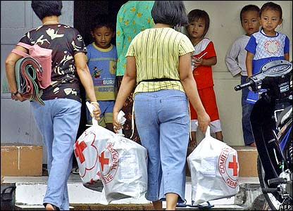 Children look at their mothers bringing back relief goods from the red cross in Sleman Yogyakarta