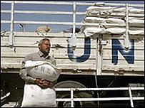 فلسطيني يحمل كيسا من الدقيق من المعونة الدولية