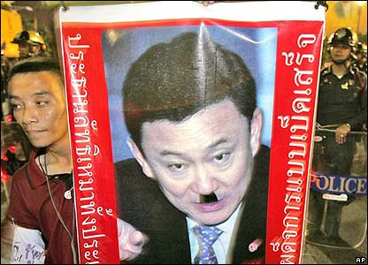Protester carrying a portrait of PM Thaksin with a Hitler moustache