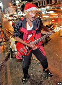 A street musician performs during protest near Sanam Luang parade grounds.
