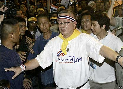 Sondhi Limthongkul, leader of the protesters, makes his way through a group of journalists.