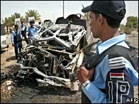 An Iraqi policeman surveys scene of destruction after the attacks near Baghdad airport