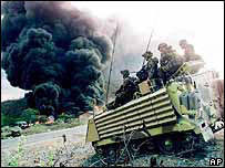 Peace Keepers from New Zealand cross a field in their light tank as an asphalt batching plant outside of Dili, East Timor burns in the distance Thursday October 7, 1999.
