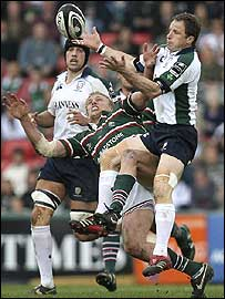Mike Catt tries to claim a high kick under pressure from Lewis Moody