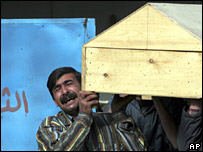 A man carries a coffin at a Baghdad mortuary