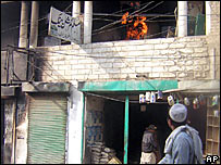 A local man in Miran Shah watches a bank attacked by militants