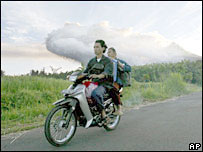 Indonesians riding a bike with the volcano in the background, 15th May