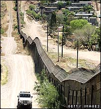 US border patrol driving along the steel wall which separates the US from Mexico