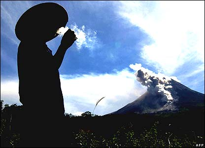 A farmer smokes a cigarette with volcano Mount Merapi in the background
