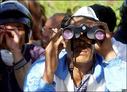 A villager uses a pair of binoculars to view the smoke