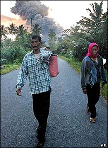 Carrying their belongings, villagers flee their homes as Mount Merapi spews hot volcanic ash