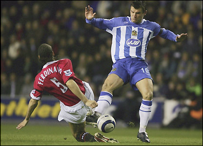 Lee McCulloch of Wigan Athletic is tackled by Rio Ferdinand