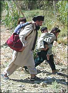 A man with children fleeing from Miran Shah town following clashes