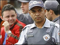 A police officer stands guard as others frisk suspects in Sao Paulo, Brazil
