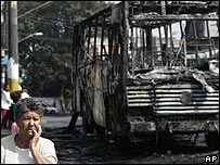 A woman walks past a burnt-out bus