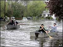 Residents on boats in the flooded town of Lowell, Mass.