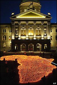 Mapa de África con velas frente a parlamento suizo.