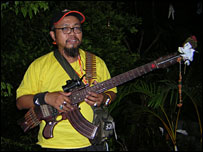 Peace activist Souriya Tawanachai, playing his 'gun guitar'