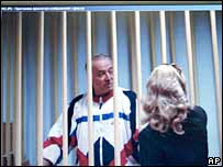 Sergei Skripal speaks to his lawyer from behind bars seen on a screen of a monitor outside a courtroom in Moscow on 9 August
