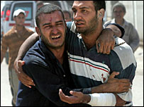 Two Iraqi men mourn the death of a relative, Baghdad, 27 July