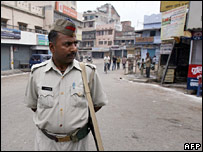 Policeman standing on deserted Varanasi street, 8 March 2006