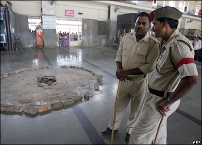 Security officials stand near bricks showing bomb damage at Varanasi Cantonment station 8 March 2006