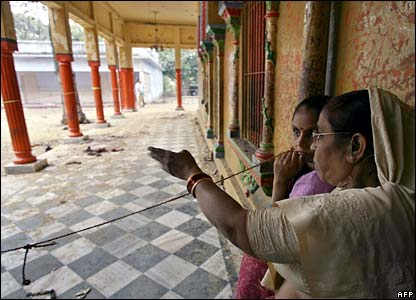 Women look at the temple blast site in Varanasi