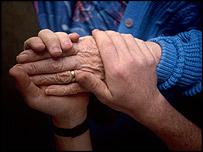 Молодой человек держит старика за руку