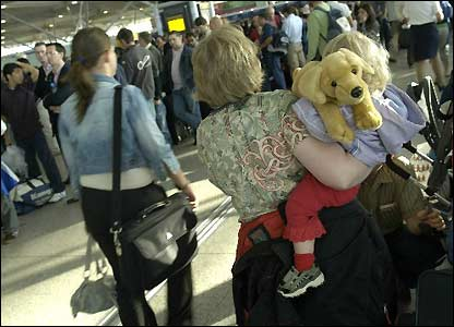 A mother carries her daughter and teddy bear at Stansted