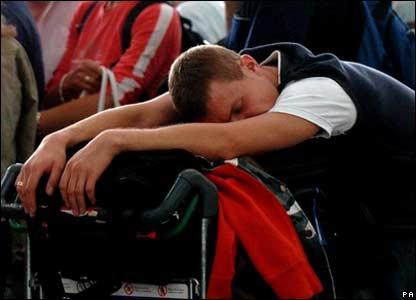 A man slumped half-asleep on his luggage trolley