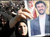 An Iranian woman holds up an image of President Mahmoud Ahmadinejad