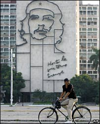 A man cycles in front of an image of Che Guevara in Havana, Cuba