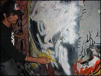 Joven de BA Stencil pinta graffiti en un muro.