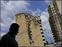 Man walks past bombed building in Tyre 10 Aug