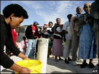 Woman collecting water from a standpipe