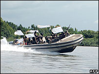 Armed Nigerian militants in a speed boat in the Niger Delta