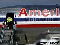 A police officer with a sniffer dog boards an American Airlines plane at Glasgow Airport on 10 August