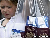 A girl holds up a plastic bag containing passports and boarding cards at Glasgow Airport 